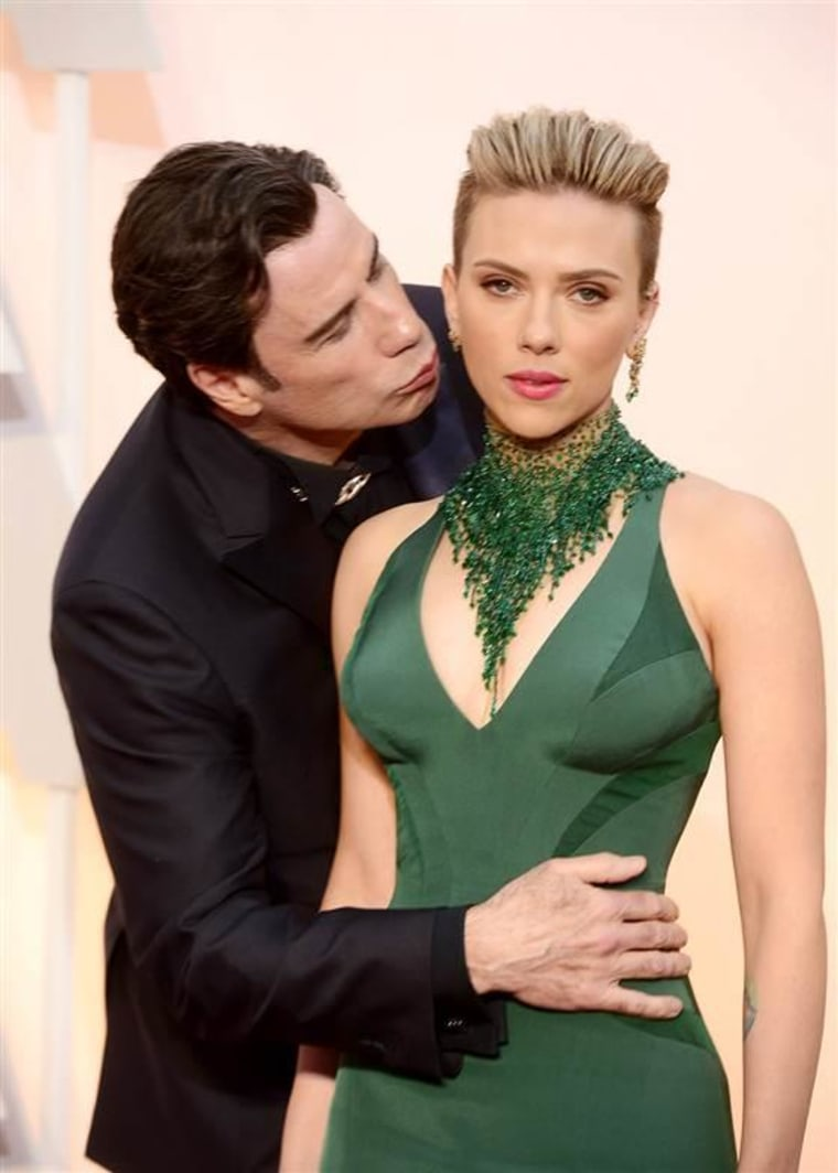 John Travolta gives Scarlett Johansson an unexpected greeting as they arrive at the 87th annual Academy Awards.
