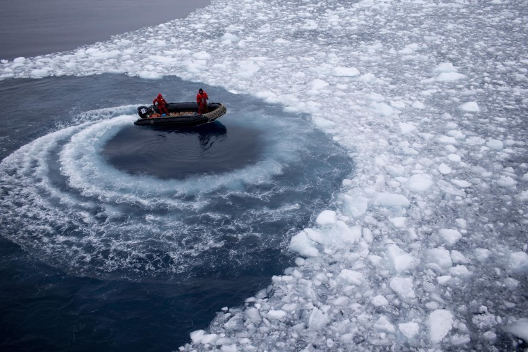 Image: Chilean Navy officers push away ice from boat