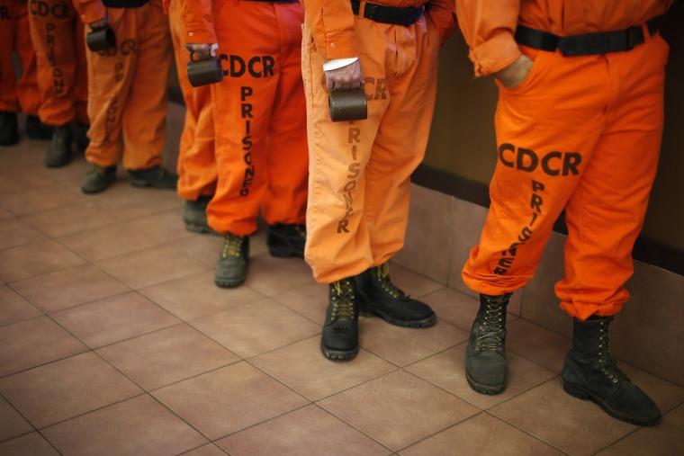 Image: Prison inmates wearing firefighting boots line up for breakfast at Oak Glen Conservation Fire Camp #35 in Yucaipa