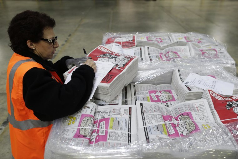 Image: An employee checks the new edition of Charlie Hebdo