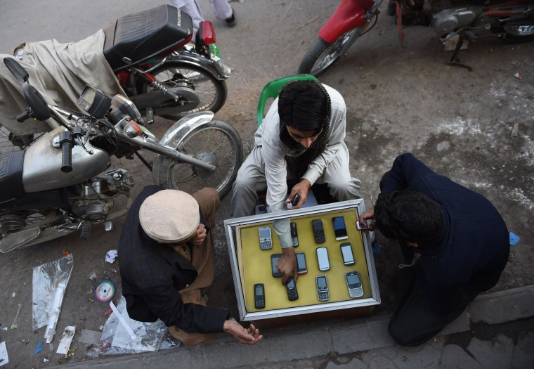 Image: A Pakistani mobile vendor sits with customers at his roadside stall