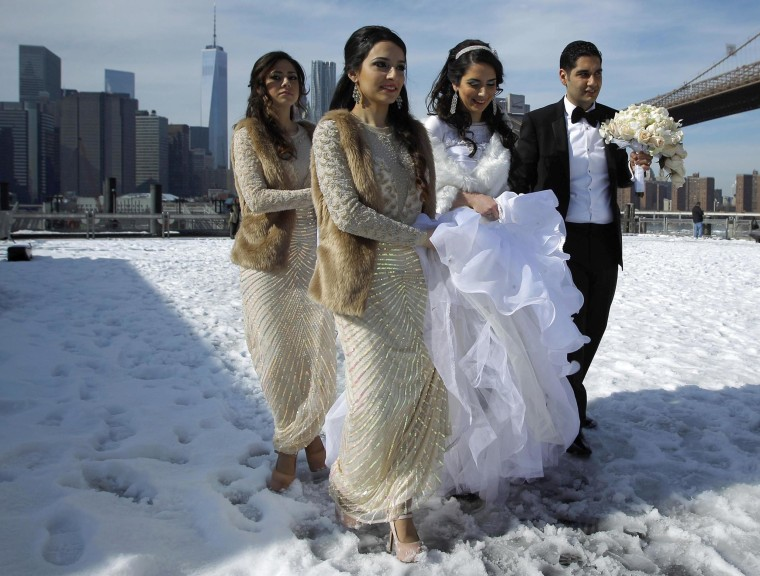 Image: A bride walks in the snow at the Brooklyn Bridge Park in New York