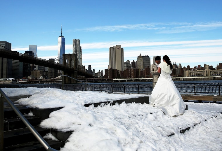 A newly wed couple poses for photographers near the East River on a cold day on Feb. 23, in New York City.