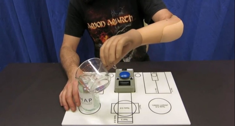 Image: Recipient of bionic hand measures a glass of water