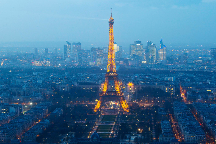 Image: A view shows the illuminated Eiffel Tower and La Defense business district in Paris