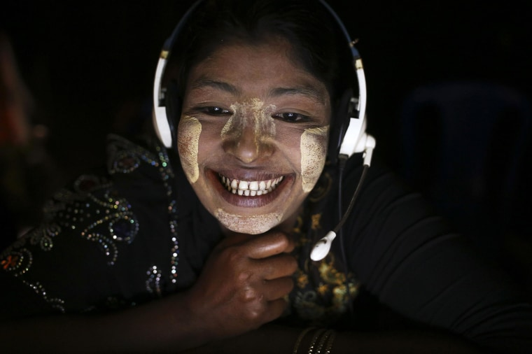Image: Sohidar, a Rohingya mother of four, enjoys an internet reunion with her husband, who works in Malaysia, from an internet hut in Thae Chaung village, near Sittwe