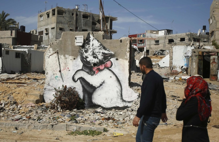 Image: Palestinians walk past a mural of a kitten, presumably painted by British street artist Banksy, on the remains of a house in Biet Hanoun