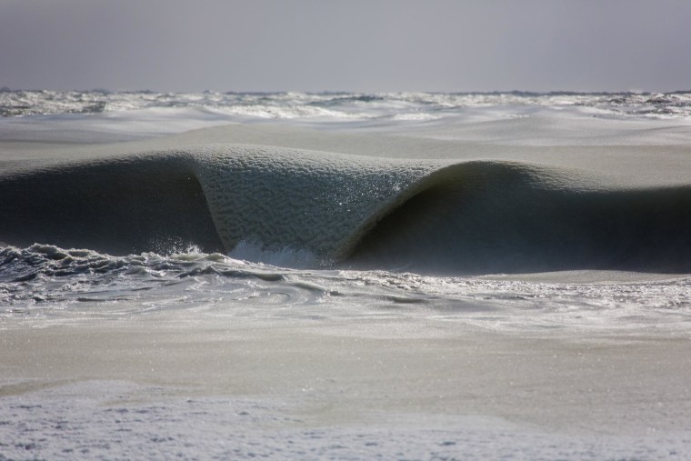 A wave, thick with ice, rolls into a beach on Nantucket, Massachusetts.