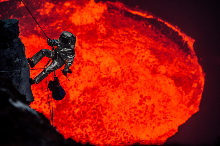 A man wearing a protective suit descends the rim of the lava lake in Marum, Vanuatu.