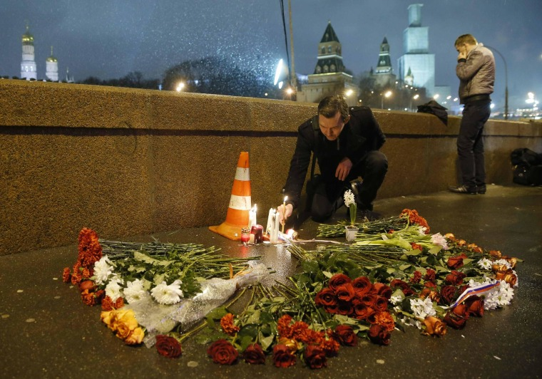Image: A man places a lit candle at the place where Boris Nemtsov was shot dead near the Kremlin in central Moscow
