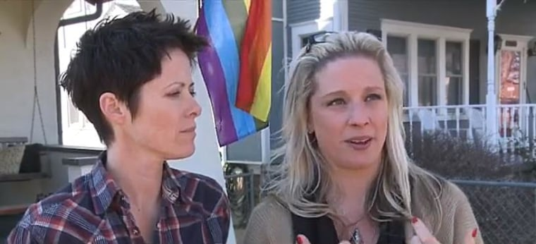 Jess Meadows-Anderson and Ariann Anderson stand in front of new rainbow flag flying from their porch after their last flag was vandalized.