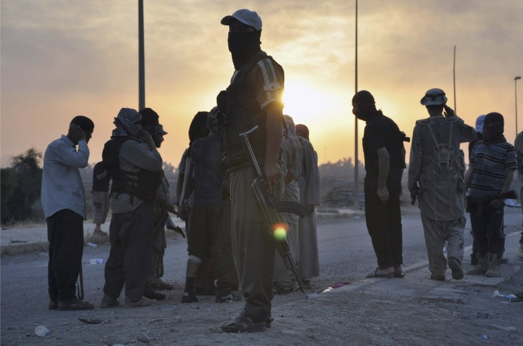 ISIS fighters stand guard at a checkpoint in the northern Iraq city of Mosul