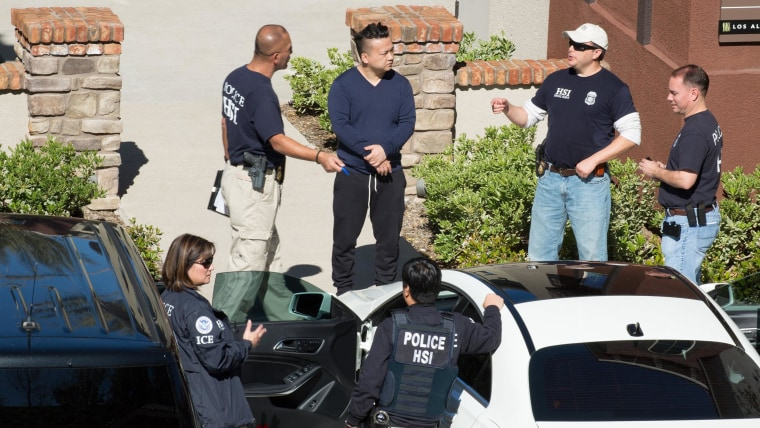 Chao Chen, center, surrounded by federal agents after his apartment in Mission Viejo, California, was raided Tuesday morning.