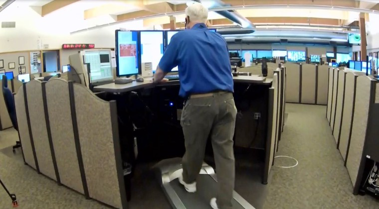 A 911 dispatcher walks on a treadmill while working in Beaverton, Ore.