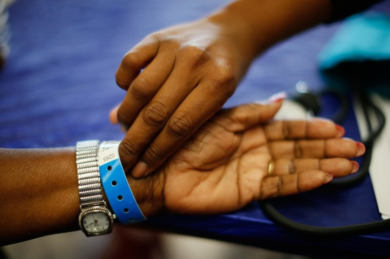 Image: Woman has her pulse taken at Care Harbor LA free medical clinic in Los Angeles
