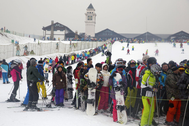 Image: Skiers and snow boarders line up as they take to the slopes of Nanshan ski resort