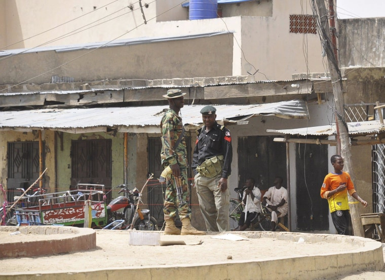 Image: Security forces stand guard at the site of bomb explosion at a market in Maiduguri