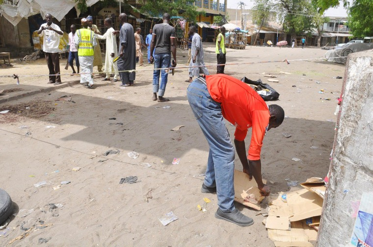 Image: People gather at the site of a bomb explosion at a market in Maiduguri, Nigeria