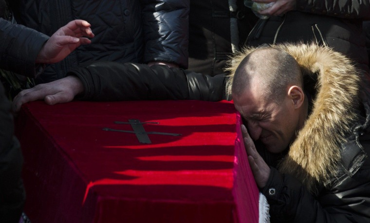 Image: Relatives pay their last respects at the coffin of a miner