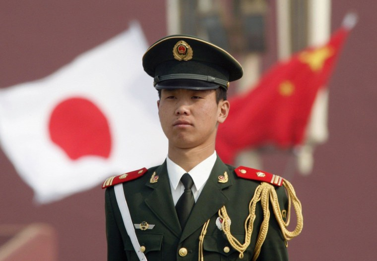 A paramilitary policeman stands guard in front of a Chinese and a Japanese flag at Tiananmen Square in Beijing in this April 29, 2009 file photo. China will welcome all national leaders to a military parade marking the 70th anniversary of the end of World War Two, the foreign minister said on March 8, 2015, the strongest sign yet that it could invite wartime enemy Japan.  REUTERS/Christina Hu/Files (CHINA - Tags: ANNIVERSARY POLITICS CONFLICT)