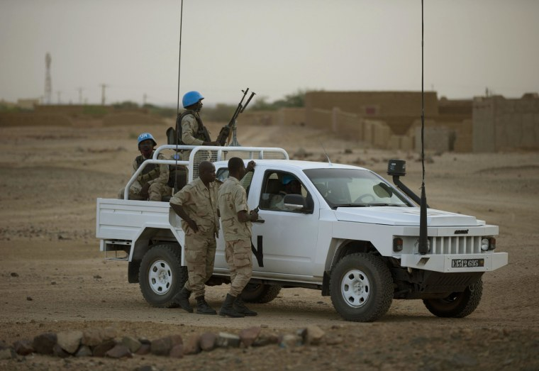 In this July 28, 2013 photo, United Nations peacekeepers stand guard at a polling station, during presidential elections in Kidal, Mali.
