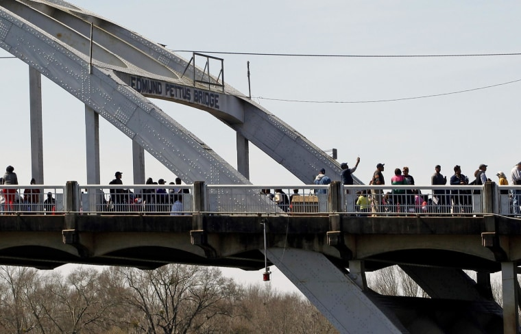 Image: People walk along the Edmund Pettus Bridge before the beginning of the 50th anniversary of the Selma to Montgomery civil rights march in Selma