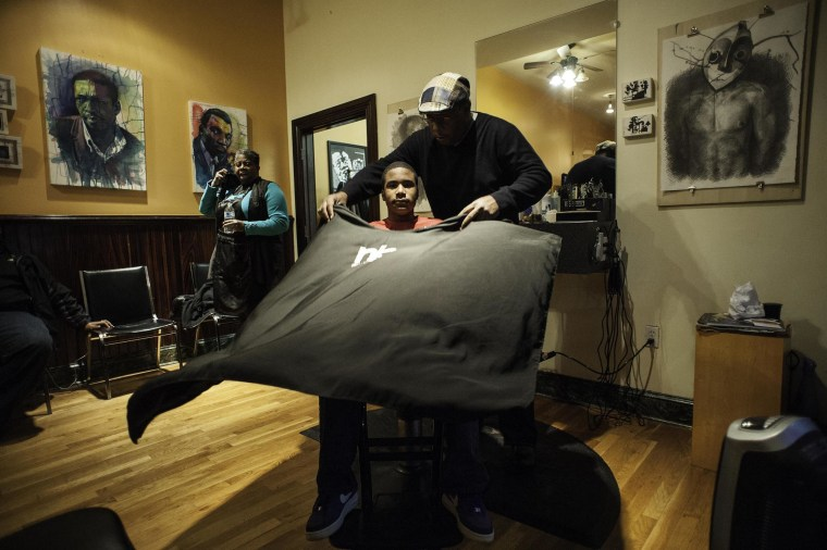 "As Dorian Walker, 15, a student at Independence High School, sits down for his haircut, he asks, ""Mr. Troy, where did you get this painting from?"" 