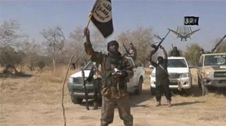 Image: Boko Haram leader Abubakar Shekau holds a flag as he delivers a message in a propaganda video