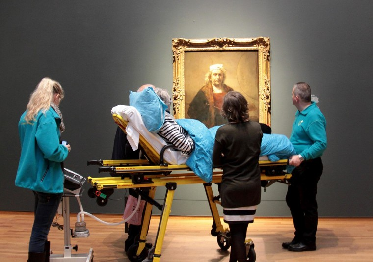 A terminally ill woman looks at a self-portrait by Rembrandt at Amsterdam's Rijksmuseum.