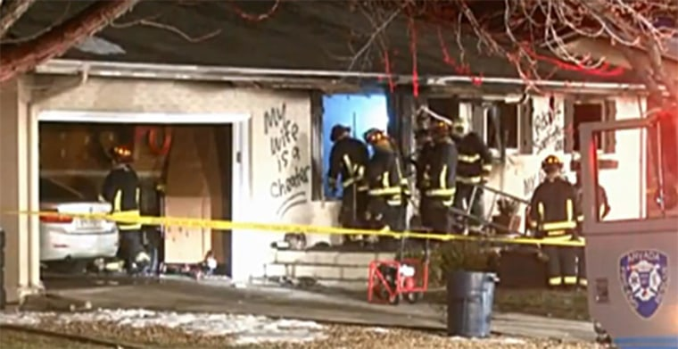 """My wife is a cheater"" is written on the side of a house as fire fighters respond to a fire in Arvada, Colo."