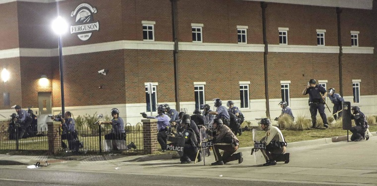 Image: Police officers respond to a fellow officer hit by gunfire outside the Ferguson Police Headquarters in Ferguson