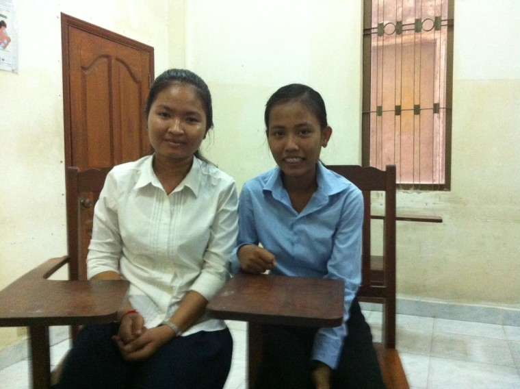 Sokunthea Vorn (left), 20, and Sophea Pheak, 17, pose for a photo in Phnom Penh, Cambodia. The two young women say they are grateful for the chance to receive an education.