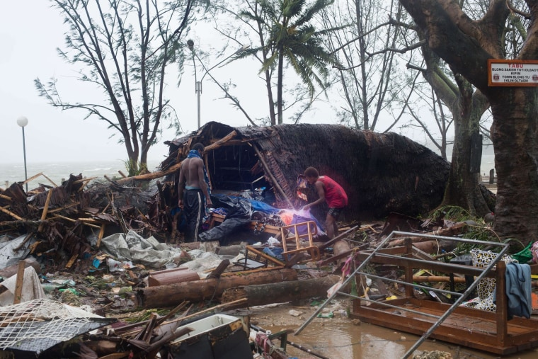 Image: Residents search through storm damage caused by Cyclone Pam.