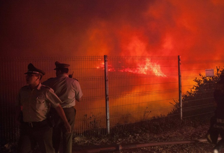 Image: Police officers standby while a forest fire burns the hills of Valparaiso city