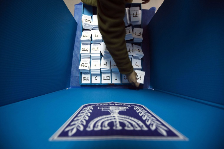 Image: Israeli soldier arranges ballots in a mobile voting booth at a border police base near Nablus