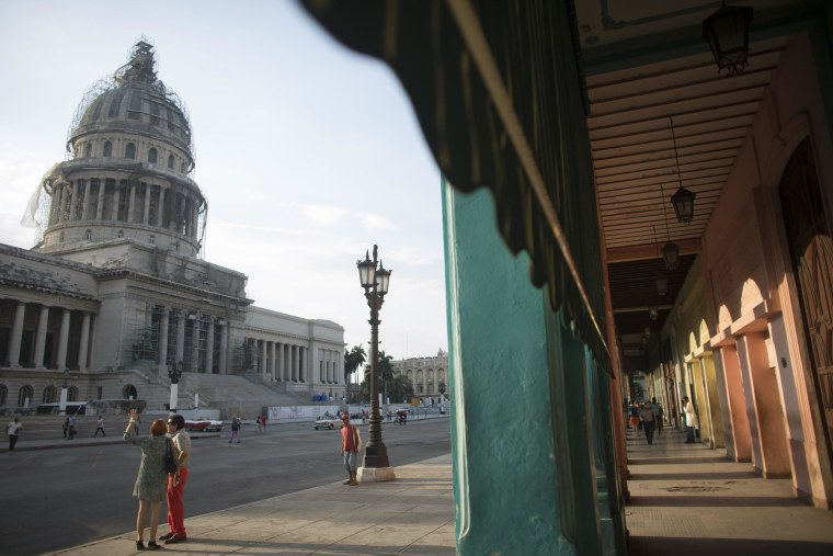 Image: Tourists stand near the Capitol in Havana