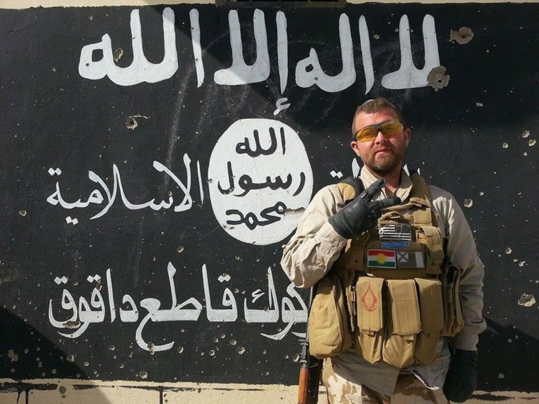 American Jeremy Woodward poses in front of an ISIS emblem painted on a wall in northern Iraq where he's joined Kurdish troops in their fight against ISIS.