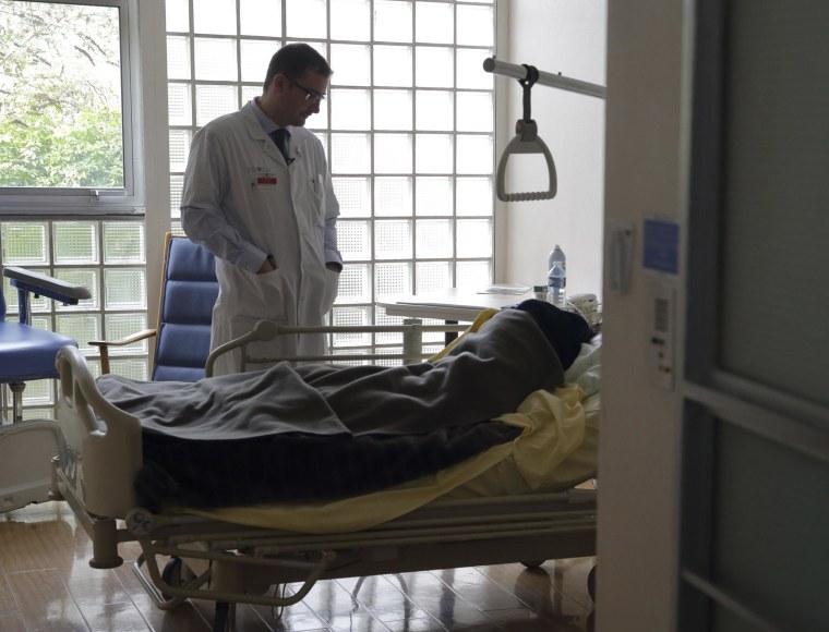 Image: Doctor Stephane Mercier visits a patient at the palliative care unit of the AP-HP Paul-Brousse hospital in Villejuif near Paris
