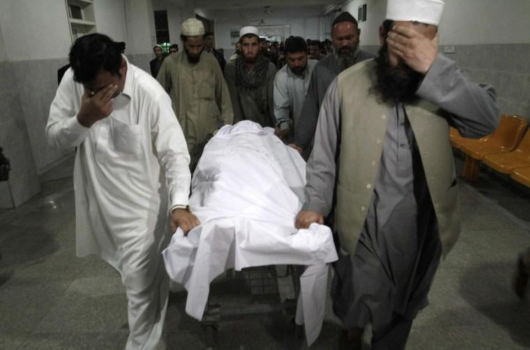 Image: Relatives move the body of Samiullah Afridi at a hospital in Peshawar
