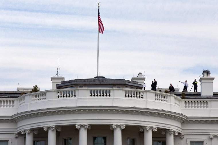 Image: Uniformed Secret Service agents patrol the top of the White House as seen from the South Lawn of the White House in Washington