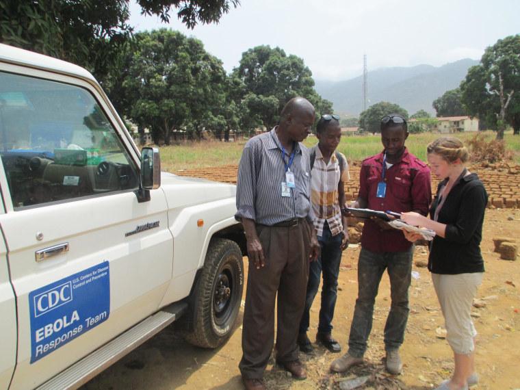Beth Ervin, a CDC epidemiologist, talks with Ebola surveillance officers: Tomeh Bangura, Ebola Surveillance Officer, Chernoh Yayah Jagitay, Ebola District Surveillance Officer and Abu Bakarr Sesay, Ebola District Surveillance Officer near Freetown, Sierra Leone.