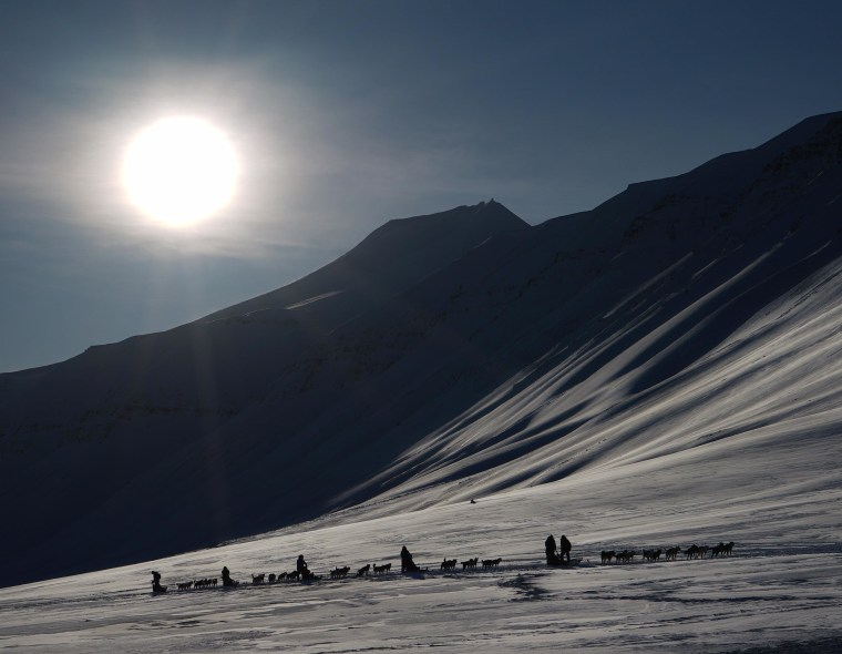 Eclipse-watching tourists ride dog sleds outside of Longyearbyen, Svalbard, on Thursday, a day ahead of the big event. The Svalbard Archipelago is one of the few spots of land that will see a total solar eclipse on Friday.