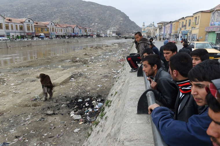 Image: Afghan residents look at the site where an Afghan woman was beaten to death