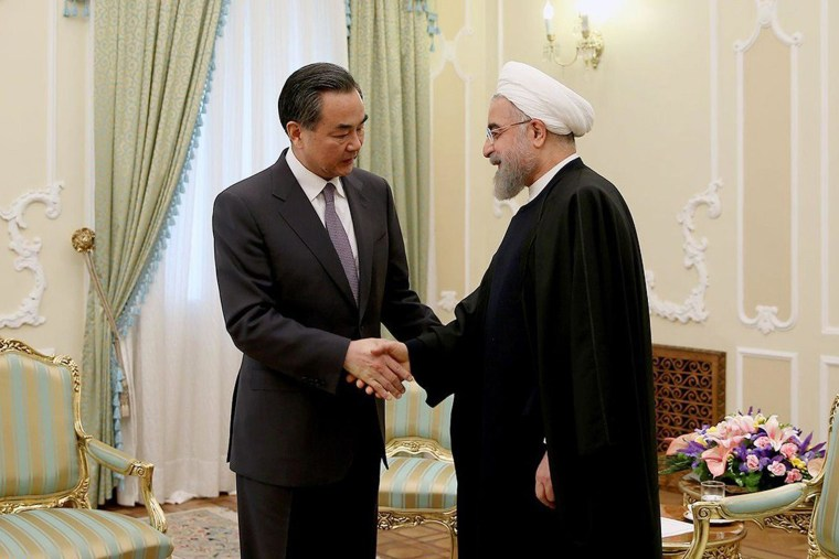 Image: Iranian President Hassan Rouhani shakes hands with Chinese Foreign Minister Wang Yi