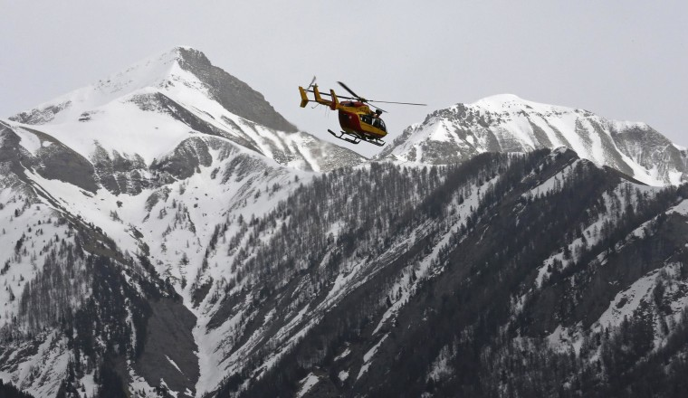 Image: A rescue helicopter from the French Securite Civile flies over the French Alps during a rescue operation following the crash of an Airbus A320