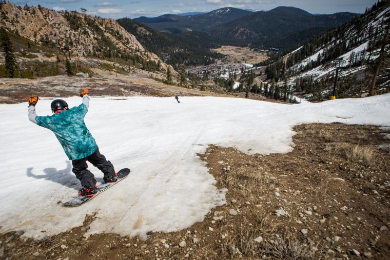 Image: Snowboarder navigates through patches of dirt