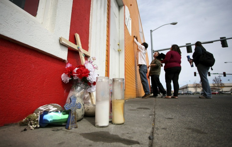 Eddie Enriquez (L) and fellow community protestors try to fix wind-damaged posters in memory of Antonio Zambrano-Montes in Pasco, Washington March 21, 2015. The afternoon before Zambrano-Montes was shot dead by police after he pelted them with rocks.