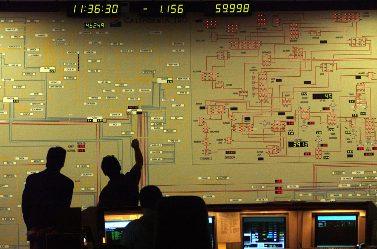 Image: People stand in front of a grid showing power distribution at the California Independent System Operator in Los Angeles, Monday, July 24, 2006