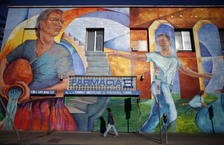Image: Man walks past a mural in the Echo Park area of Los Angeles, home to many Mexican and Central American migrants, in California