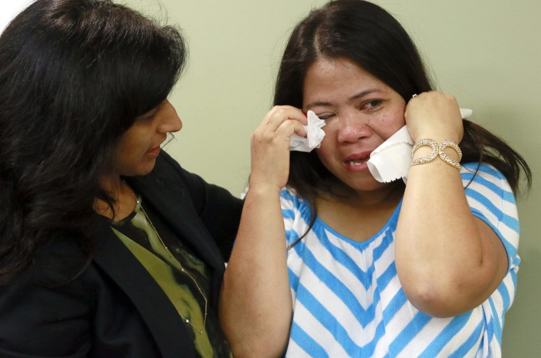 Gina Pablo (right), one of the 11 workers suing L'Amande bakery, is consoled by litigation director Laboni Hoq during a news conference at Asian Americans Advancing Justice in Los Angeles on Thursday, March 19, 2015.
